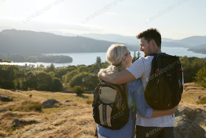 Rear View Of Couple Standing At Top Of Hill On Hike Through Countryside In Lake District UK