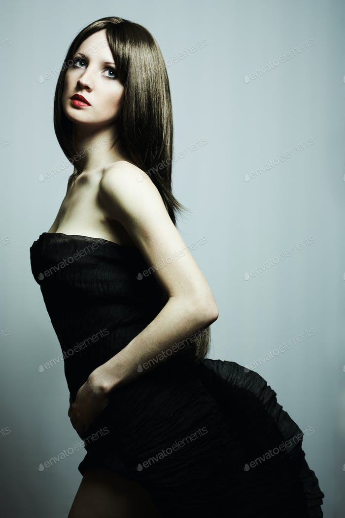 Fashion portrait of young beautiful elegant woman in the black d
