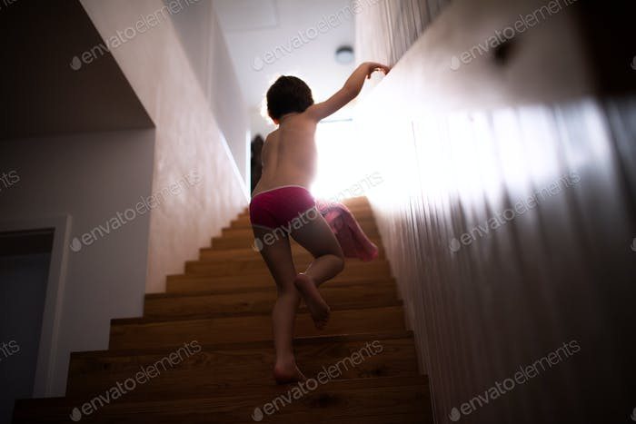 A rear view of small child walking up the stairs