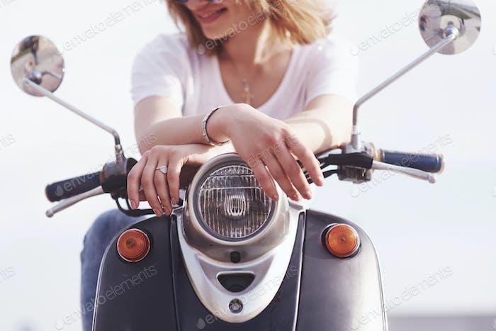 Mädchen Hipster sitzt auf einem schwarzen Retro-Scooter, lächelnd posiert und genießen Sie die warme Frühlingssonne
