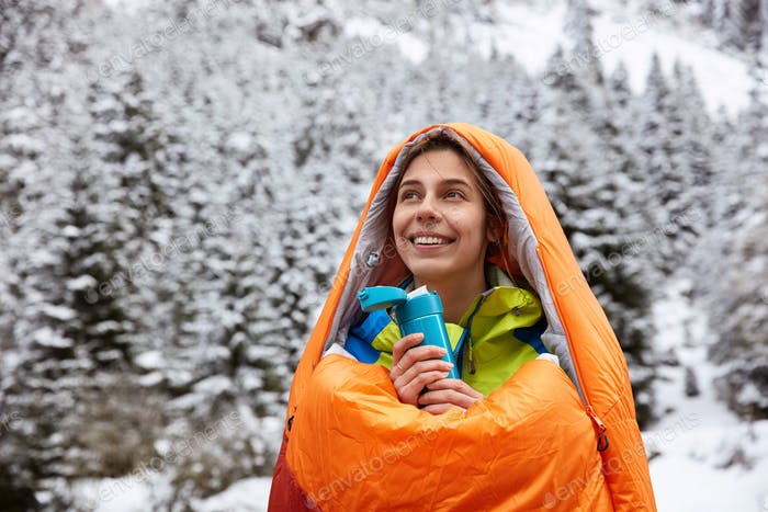 Happy female hiker warms after climbing mountain, wrapped in orange sleeping bag, poses over mountai