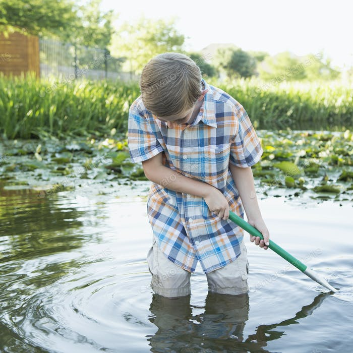 A young boy standing thigh deep in water, using a net to scoop finds from the river