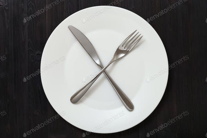 Draufsicht der weißen Platte mit Kulterie auf dunkelbraun