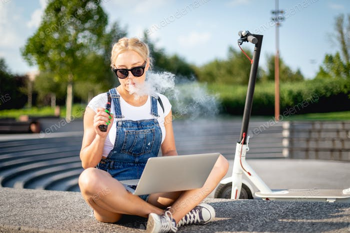 Woman smoking e-cigarette using her laptop computer while sitting at street with electric scooter