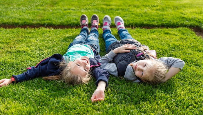 Two smiling kids lying on the grass