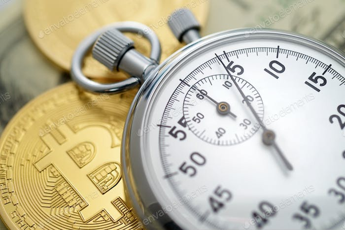 Physical golden bitcoin coins and mechanical analog stopwatch.