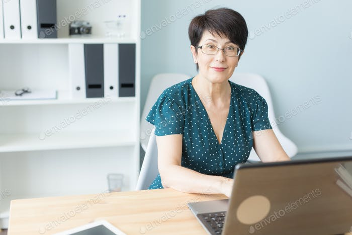 Thumbnail for Business, technology and people concept - middle aged woman work in office and use a laptop