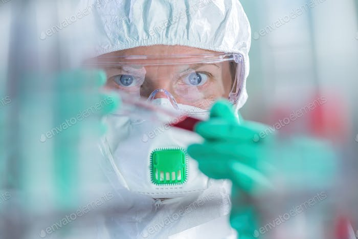 Virologist healthcare professional analyzing blood test sample in lab tubes