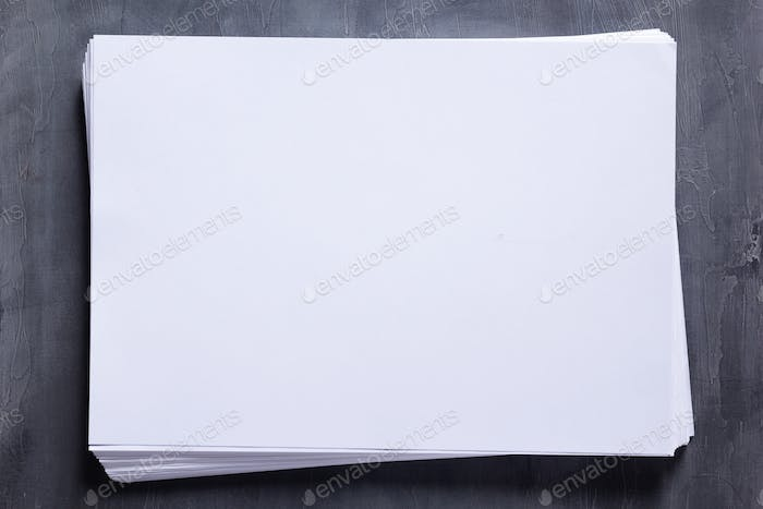 Stack of paper sheet with empty pages on table background. Creative idea concept