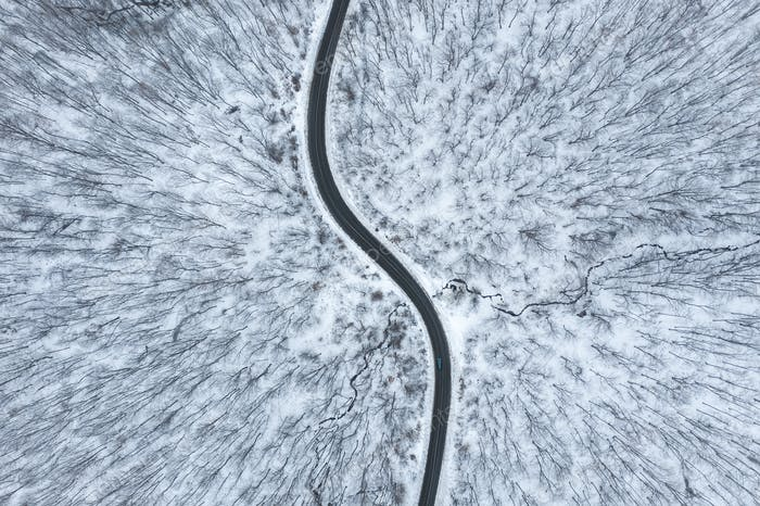 Beautiful winter forest road seen from above. Aerial drone shot