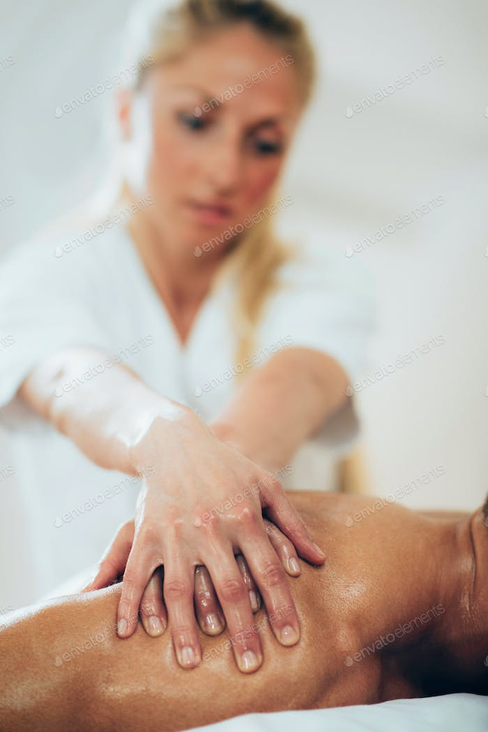 Physical therapist doing massage of shoulders