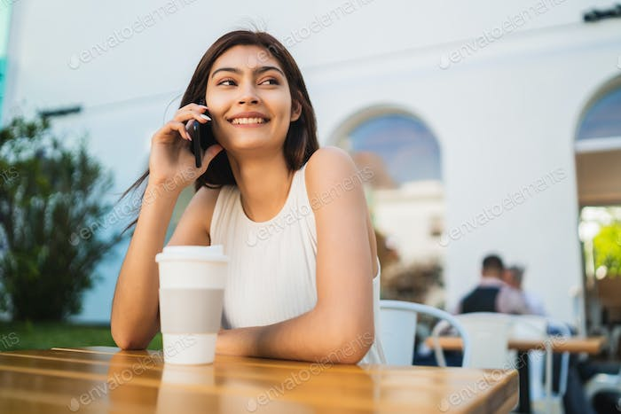 Young latin woman talking on the phone.