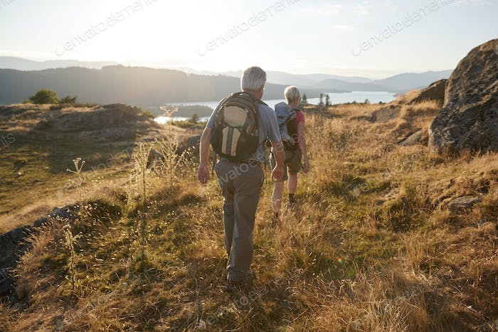 Rear View Of Senior Couple Walking On Top Of Hill On Hike Through Countryside In Lake District UK