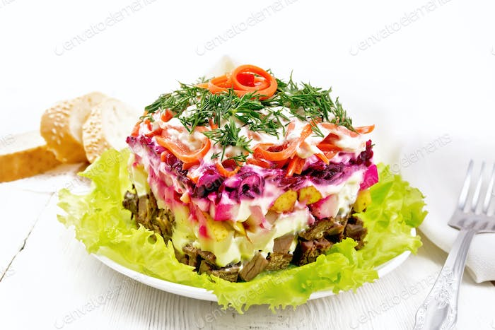 Salad with beef and vegetables on light wooden table