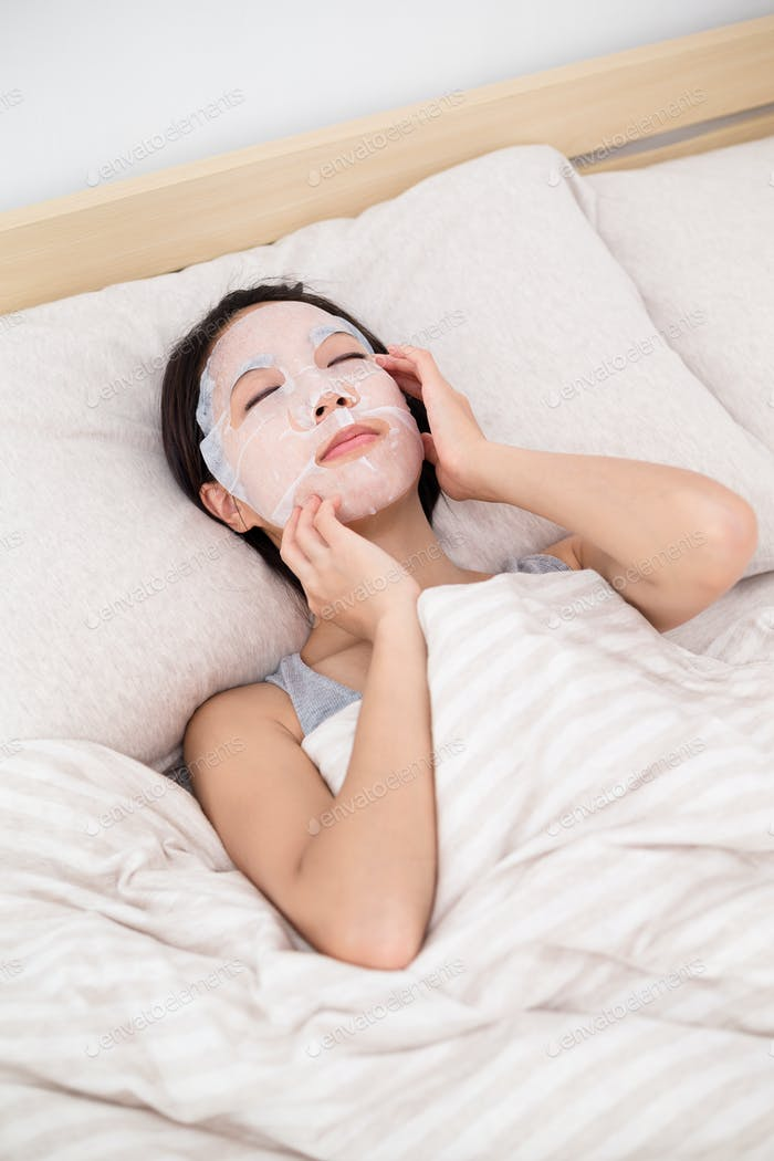 Woman lying down in bed with facial mask sheet