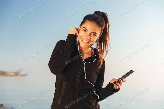 Happy young sportswoman listening to music