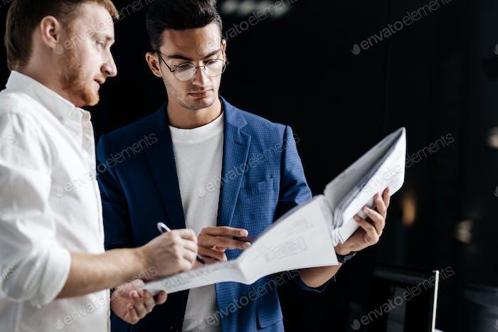 Zwei professionelle Architekten diskutieren Blatt mit Zeichnung im Büro