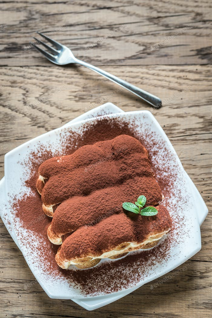 Tiramisu on the plate on the wooden background