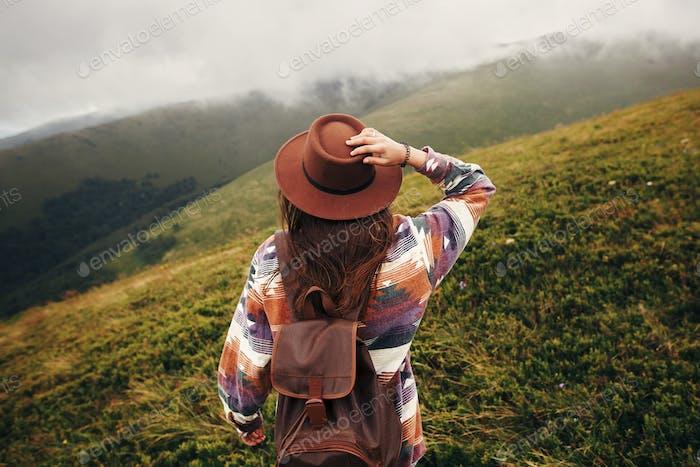 Traveler Mädchen im Hut mit Rucksack Blick auf die sonnigen Berge in Wolken