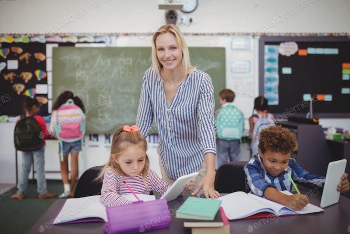 Teacher helping schoolkids with their homework in classroom