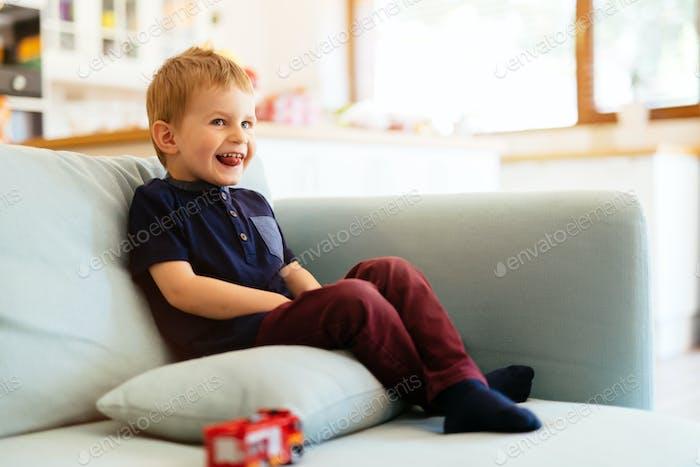 Happy boy sitting on sofa in living room