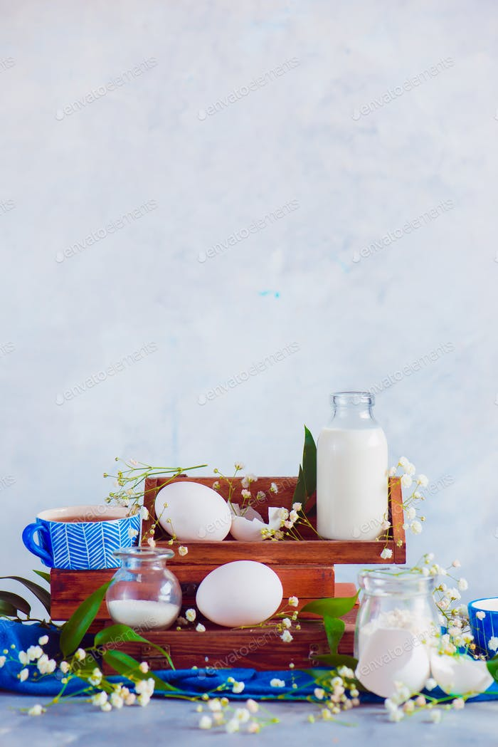 Home cooking concept with baking ingredients, eggs, milk, flour on a light background. Wooden boxes