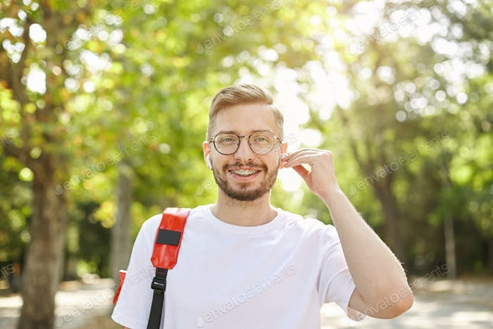 Good looking young bearded man looking to camera with wide smile, wearing eyewear and headphone