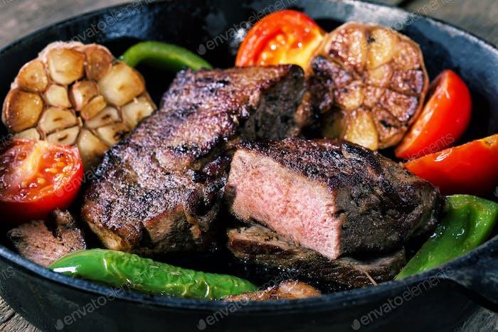 Appetitliches Rindfleischsteak in einer Pfanne mit Gemüsegarnitur