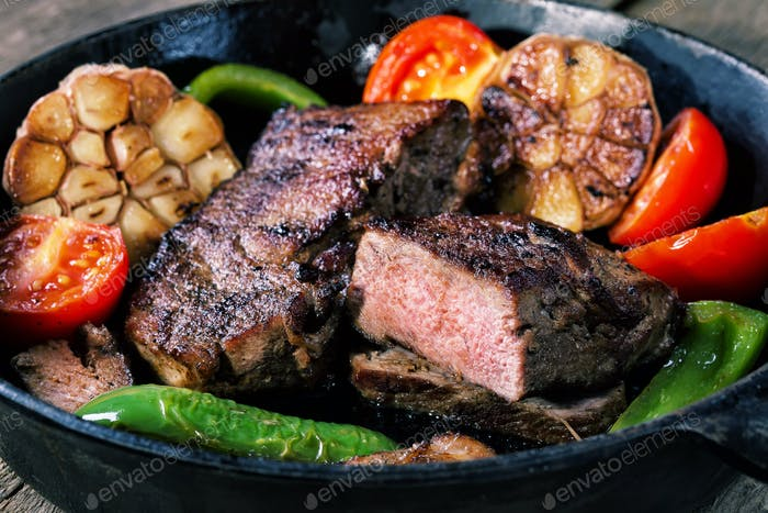 Appetizing beef steak in frying pan with vegetable garnish