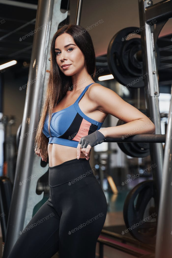 Sportswoman with slim figure posing with barbell behind