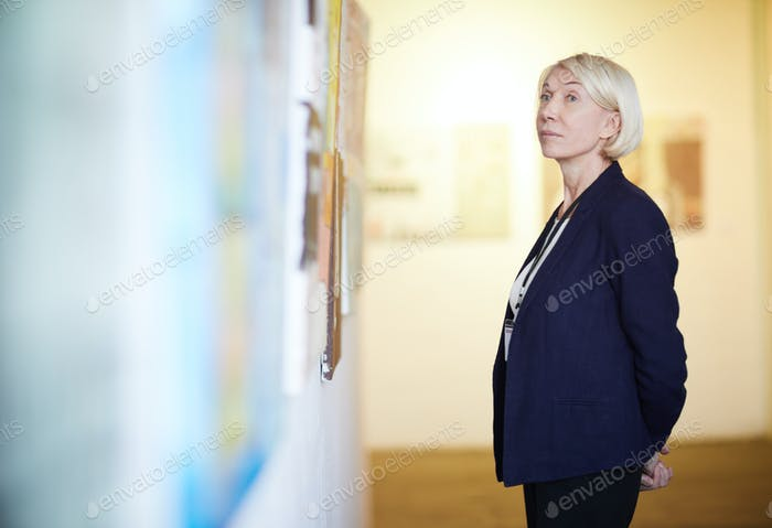 Mature Woman Looking at Paintings