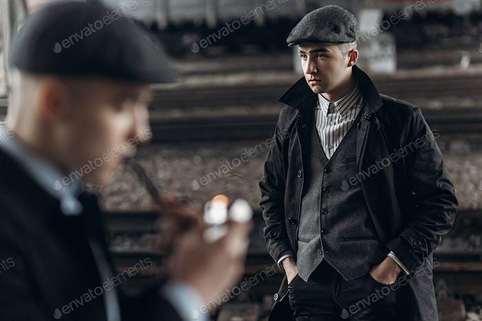 Brutale Gangster posieren auf dem Hintergrund der Eisenbahn