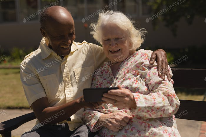 Front view of happy senior couple using mobile phone and sitting on bench in garden
