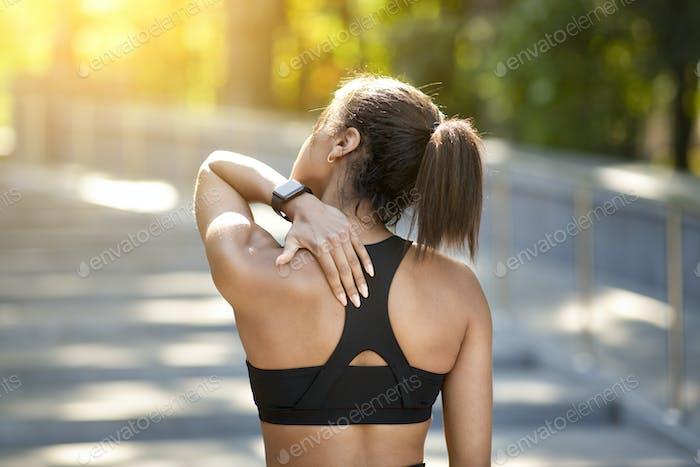 Rückansicht von schwarzen sportlichen Mädchen reiben ihre Wirbelsäule