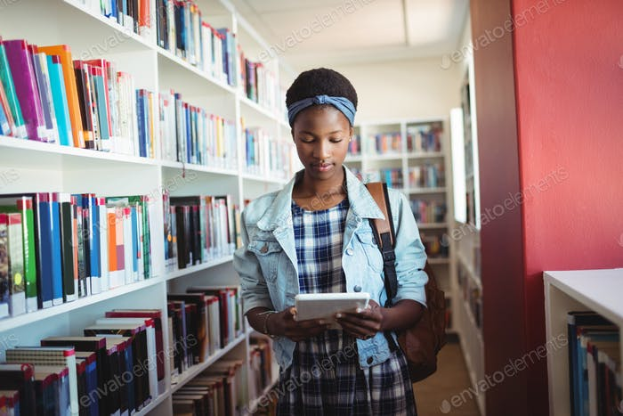 Attentive schoolgirl using digital tablet in library