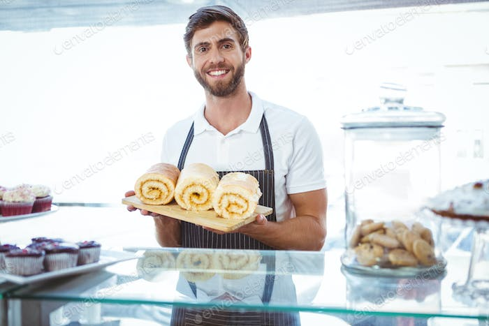Smiling worker holding pastry behind the counter at bakery