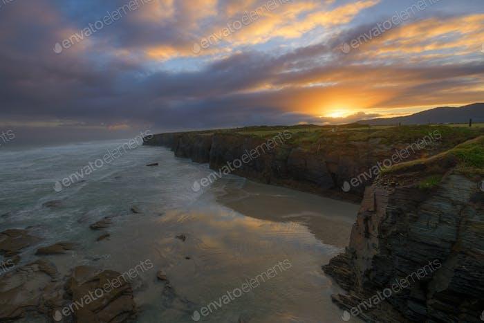 Goldene Wolken bei Morgendämmerung am Strand