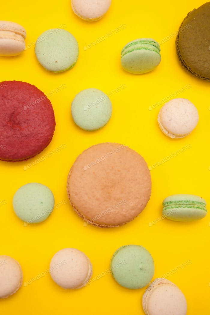 Delicious big caramel macaroon flavour next to cherry macaroon over yellow background