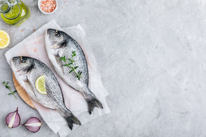 Fresh raw dorado fish with spices. Ingredients for cooking or grill on cutting board.