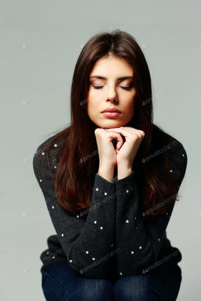 Portrait of a young pensive woman with closed eyes