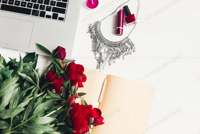 laptop with notebook, stylish necklace and beautiful red peonies