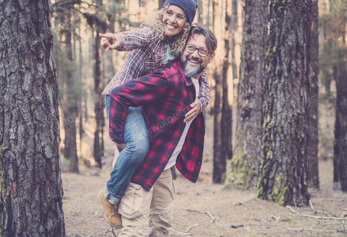 Verspieltes glückliches gutaussehendes kaukasisches Paar, das Huckepack beim Gehen auf dem Weg im Wald hat