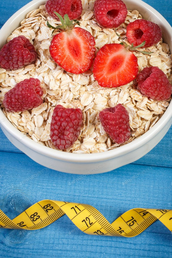 Oat flakes or oatmeal with fruits and tape measure, healthy lifestyle and nutrition concept