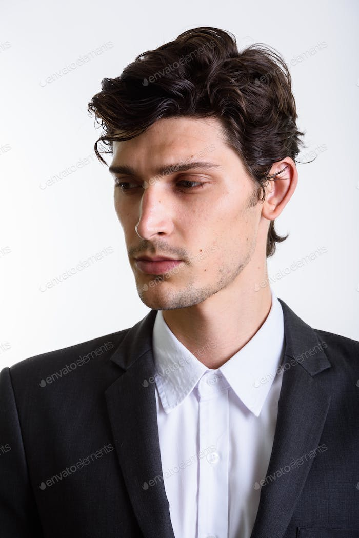Studio shot of young handsome businessman looking down