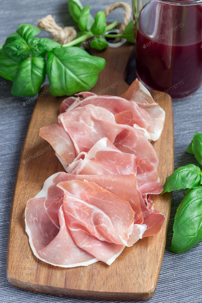 Prosciutto ham on wooden board, basil leaves on background, vert