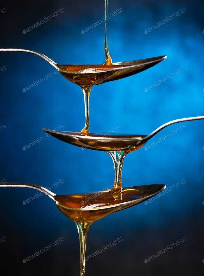 Goldener süßer Honig verschüttet über bunten Hintergrund