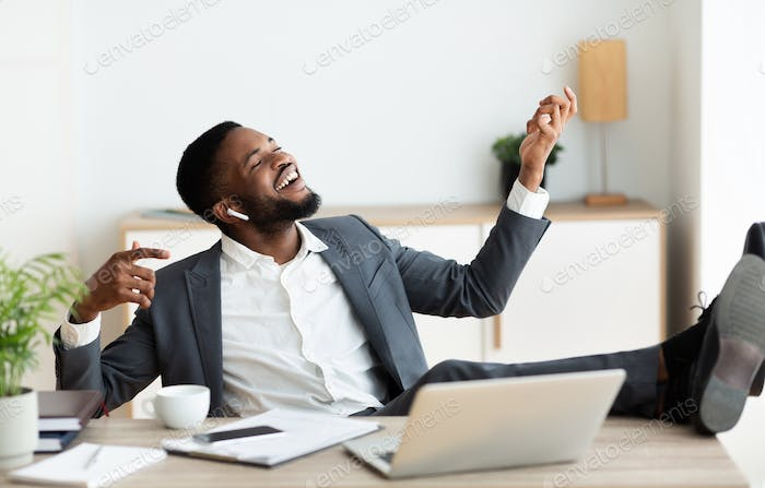 Happy african businessman listening to music with legs on table
