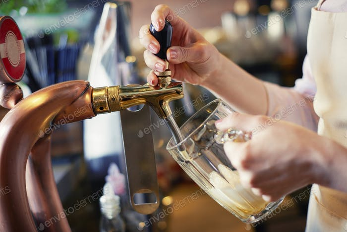 Close up of bartender pouring pint of beer