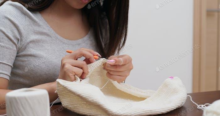Woman knits crochet at home