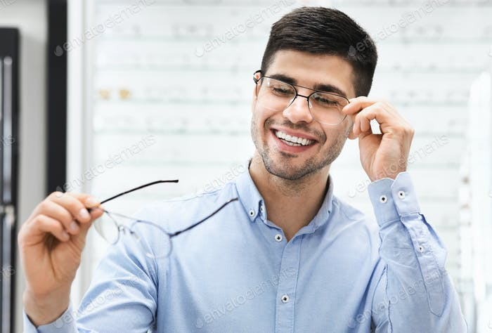 Portrait of handsome young man choosing spectacles